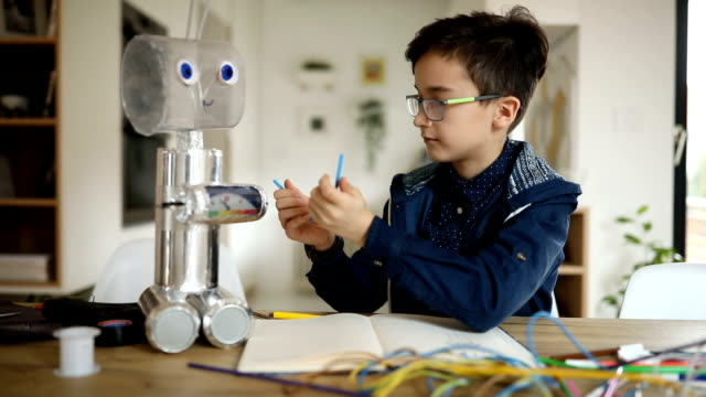 smart young boy engineer constructing a robot alone - occhiali da vista video stock e b–roll