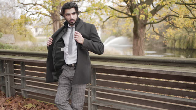 a smart young man in the park wearing a coat style jacket - handsome people stock videos & royalty-free footage
