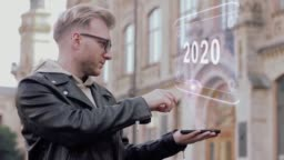 Smart young man with glasses shows a conceptual hologram 2020