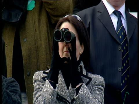 Smartly dressed racegoer looks through binoculars 2003 Grand National