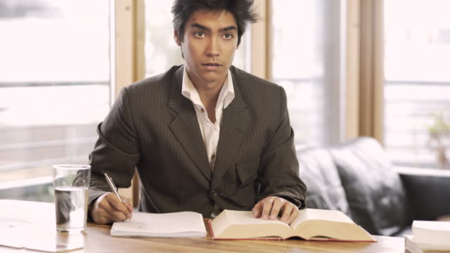 A smartly dressed young man sitting at a desk writing. Then looks up as if to catch someones eye.