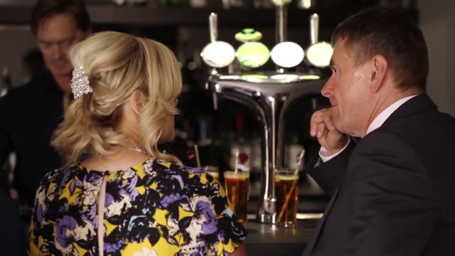 a smartlydressed middle aged couple drinking and chatting at the bar during a party no - two parents stock videos & royalty-free footage