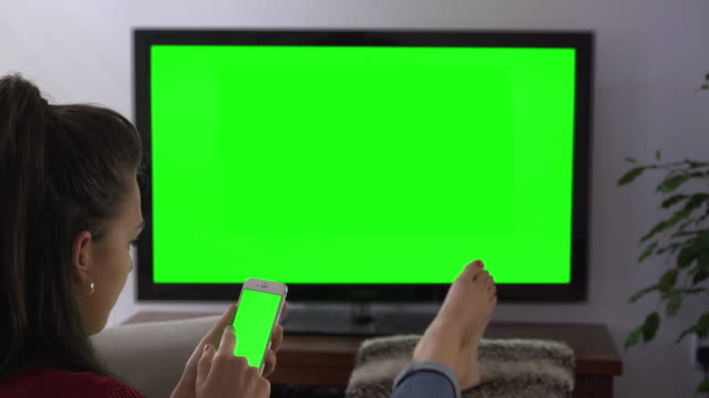 Smartphone and tv chromakey screens, young woman feet up.