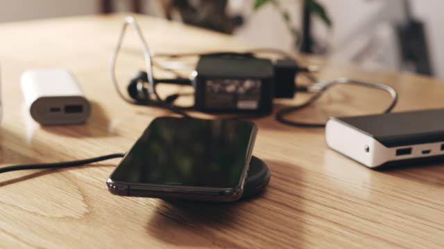 vidéos et rushes de chargement ms smartphone sur un chargeur de téléphone mobile sans fil - batterie
