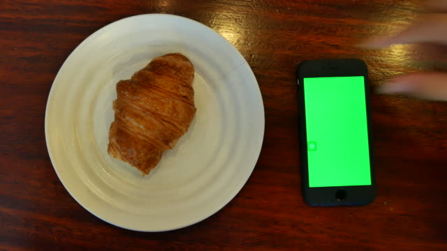 smartphone green screen with croissant on wood table - froth art stock videos and b-roll footage