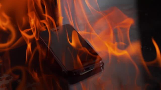 vídeos de stock e filmes b-roll de slo mo smartphone in flames on black surface - burning