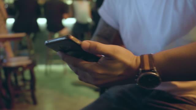 スマートフォンでパブレストラン - 腕時計点の映像素材/bロール