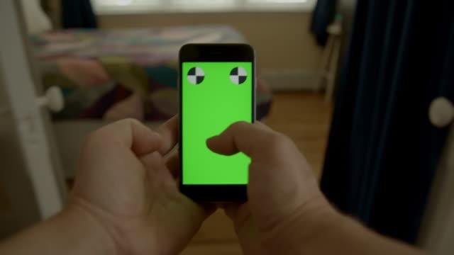 Smartphone man hand sms'en surfen binnen huis groen scherm