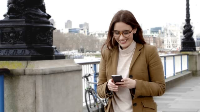 Smartphone message, smiling woman walking.