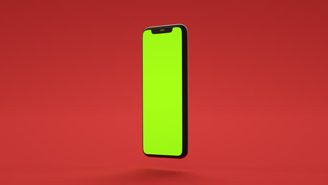 smartphone mockup with green chroma key screen on red background. - coloured background stock videos & royalty-free footage