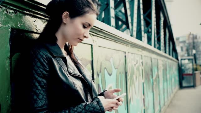 スマートフォンのテキスト、立っている女の子、街のブリッジ、グラフィティ。