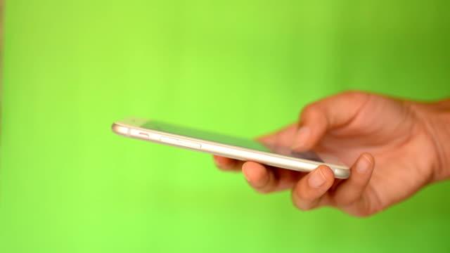 vídeos de stock, filmes e b-roll de smartphone touchscreen com tela verde - agarrar