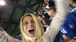 Smartphone video of a woman jumping out of her seat at the stadium and cheering for her team