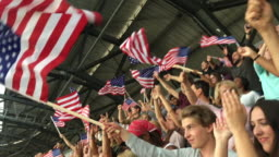 Smartphone video of the audience cheering with USA flags in the stadium