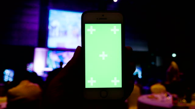 Smartphone with green screen at Night Party