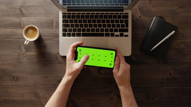 vidéos et rushes de smartphone avec l'écran vert sur un bureau de travail - table top view