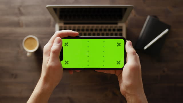 smartphone with green screen on a work desk - table top view stock videos & royalty-free footage