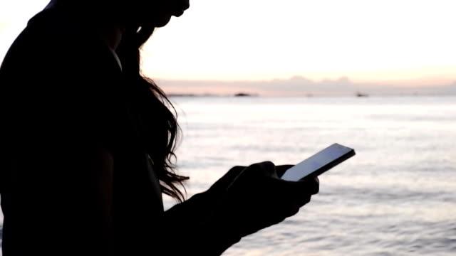 smartphone-frau mit app am smartphone am strand sonnenuntergang. mobile handy hautnah. - weibliche angestellte stock-videos und b-roll-filmmaterial