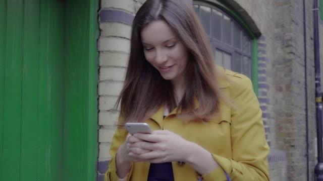 Smartphone jonge vrouw buitenshuis.