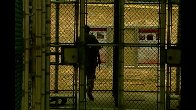 smears guantanamo bay detainees requested by britain; r12090610 cuba: guantanamo bay naval base: camp delta: ext prison guard along behind mesh gate... - prison guard stock videos & royalty-free footage