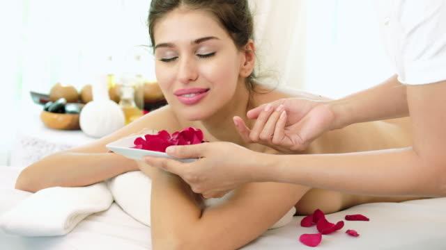 riechen sie eine rose, schöne frau zum entspannen im spa. - schönheitssalon stock-videos und b-roll-filmmaterial