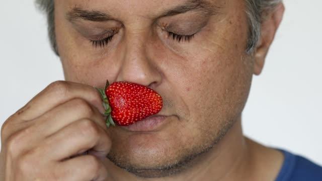 stockvideo's en b-roll-footage met ruikende aardbei - menselijke neus