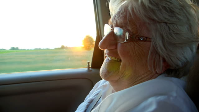 Smile senior women in the car at sunset