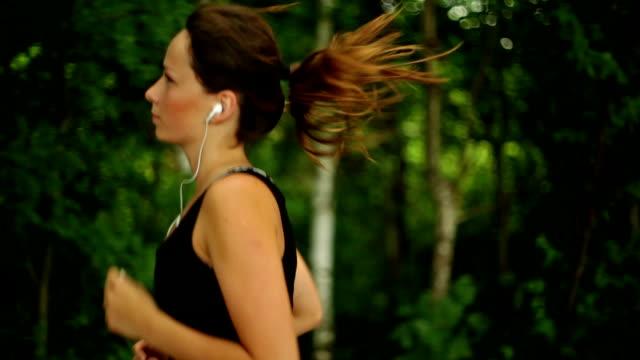 vídeos de stock, filmes e b-roll de sorriso jovem mulher correndo no parque - fazendo cooper