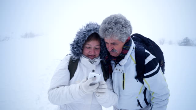 stockvideo's en b-roll-footage met glimlachte senior paar selfie te nemen in de winter natuur - zelfportret fotograferen