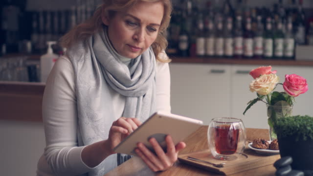smiley mature woman using digital tablet while drinking tea - affectionate stock videos & royalty-free footage