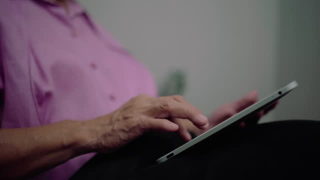lächelnde 60er jahre ältere frau mit tablet, stehend in der nähe des fensters. - mittlerer teil stock-videos und b-roll-filmmaterial