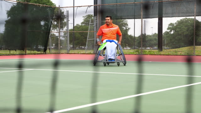 MS Smiling adaptive athlete making forehand shot during wheelchair tennis match