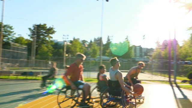 ms smiling adaptive athlete shooting basketball during game on outdoor court - wheelchair basketball stock videos and b-roll footage
