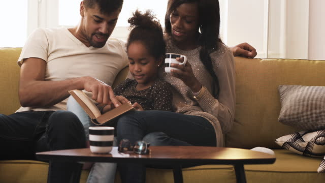 smiling african american family storytelling and enjoying a day together at home. - african american ethnicity stock videos & royalty-free footage