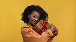 smiling african american woman holding gift isolated on yellow