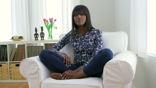 smiling african american woman sitting cross legged on couch - cross legged stock videos & royalty-free footage