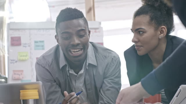 Smiling African businessman discussing plans with coworkers in office