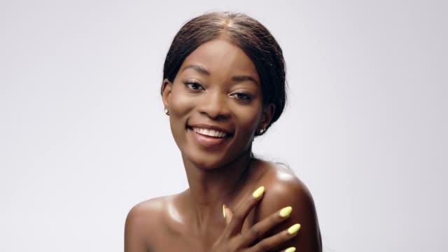 stockvideo's en b-roll-footage met glimlachend afrikaanse etniciteit vrouw gezicht huidverzorging. gladmakende huid - breekbaarheid