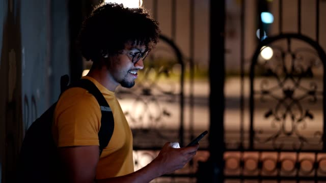 smiling african student texting outside - film montage stock videos & royalty-free footage