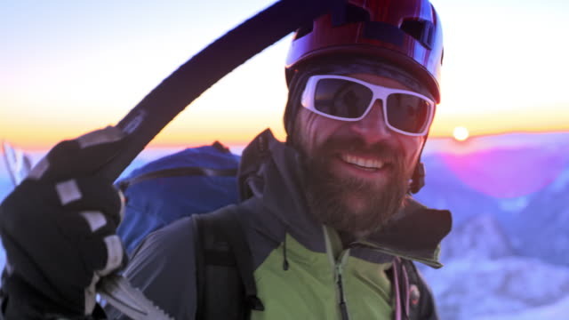 smiling alpinist on the snowy mountain top at sunset - ski goggles stock videos & royalty-free footage