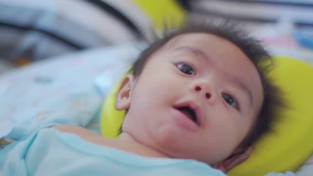 leende och söt liten pojke på sängen. - endast en pojkbaby bildbanksvideor och videomaterial från bakom kulisserna