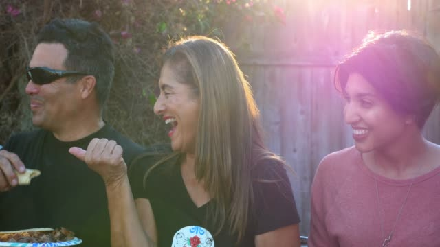 vidéos et rushes de ms smiling and laughing family dining together during backyard barbecue - repas