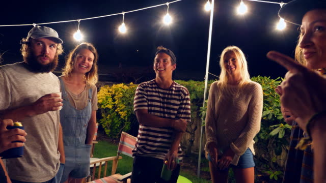 MS Smiling and laughing group of friends drinking beer during backyard party on summer evening