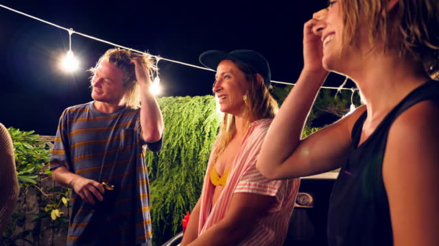 PAN Smiling and laughing group of friends in discussion during backyard party on summer evening