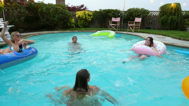 ms td smiling and laughing group of friends playing in backyard pool on summer evening - inflatable stock videos & royalty-free footage