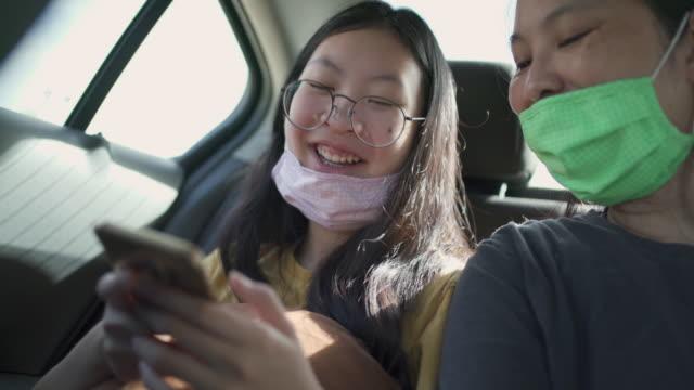 covid-19コロナウイルスの状況の間にフェイスマスクで車の中で笑って笑う - タクシー点の映像素材/bロール