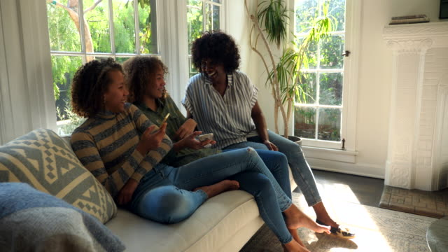 ms smiling and laughing mother and daughters sitting on couch in living room looking at smartphones - schwester stock-videos und b-roll-filmmaterial