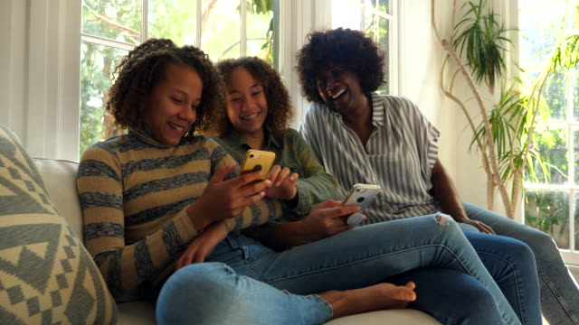 ms smiling and laughing mother and daughters sitting on couch in living room looking at smartphones - sibling stock videos & royalty-free footage