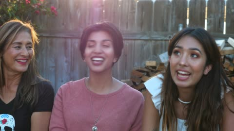 vidéos et rushes de ms smiling and laughing sisters in discussion with family members during backyard barbecue - 65 69 ans