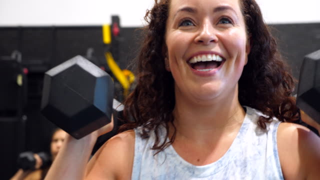 cu smiling and laughing woman doing dumbbell lunges during fitness class in gym - effort stock videos & royalty-free footage